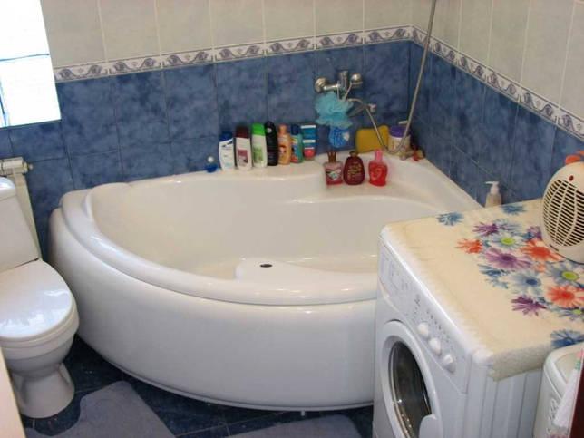 вариант современного интерьера ванной комнаты с угловой ванной